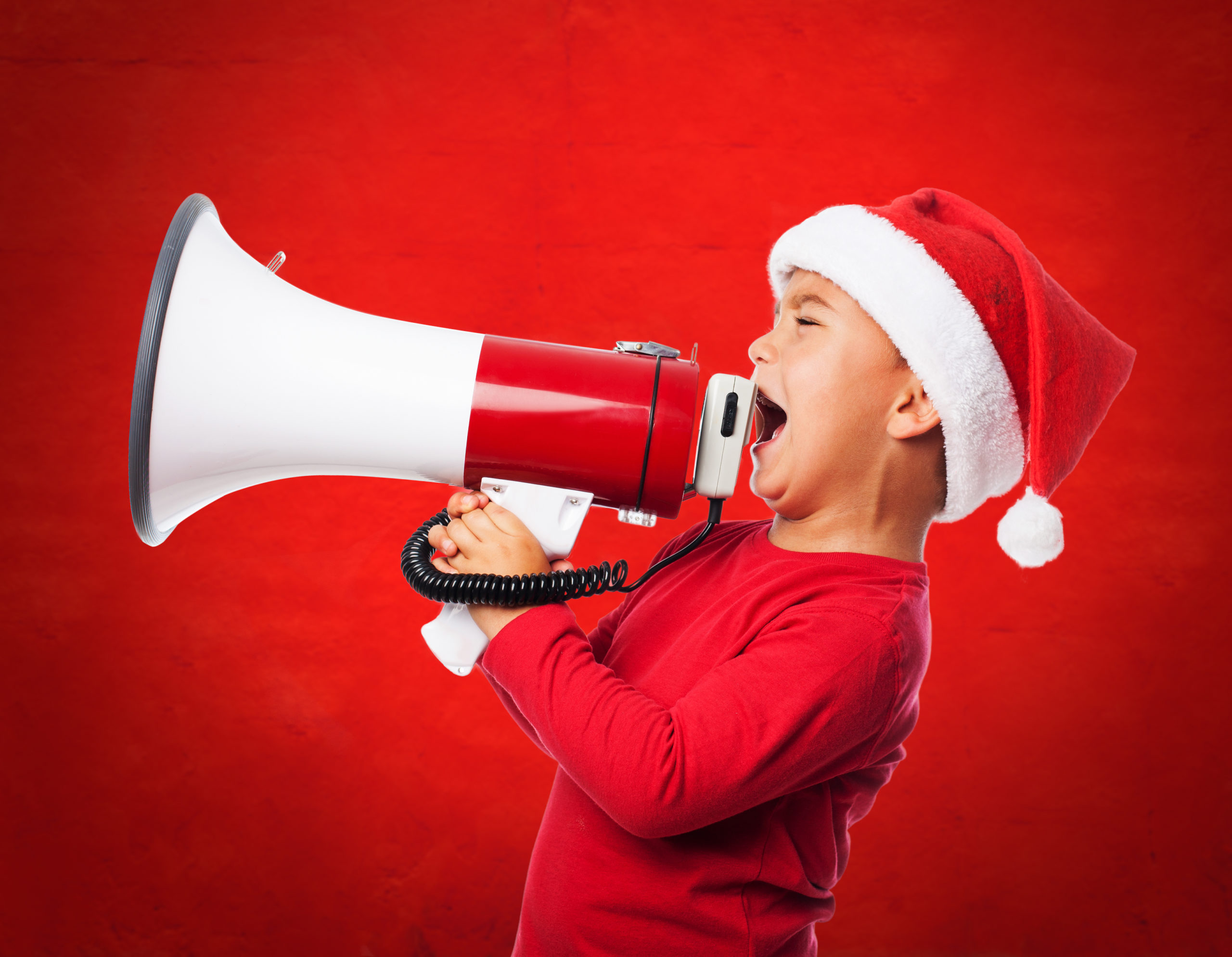child wearing santa hat and shouting with megaphone scaled - CASAL DE NADAL